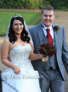 groom and bride holding black baccara wedding flowers