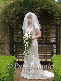 Bride with shower bouquet in grounds of the Welcombe Hotel, Stratford upon Avon