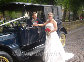 Bride standing by wedding car outside St Mary's Guildhall, Coventry