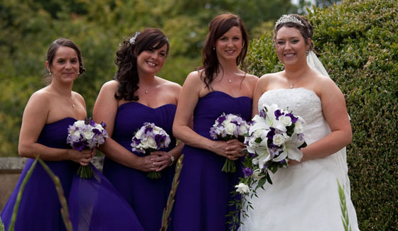 bride and bridesmaids holding deep purple wedding flowers at Wroxall Abbey