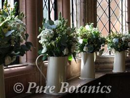 Enamel jugs containing vintage wedding flowers on the window sills at Kenilworth Castle