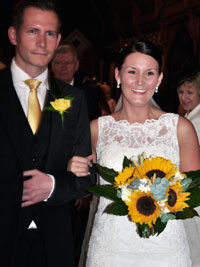 bride and groom walking down the aisle with yellow wedding flowers