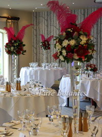 tall centrepieces at wedding reception, featuring pink feathers