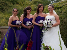bride and bridesmaids holding purple wedding bouquets