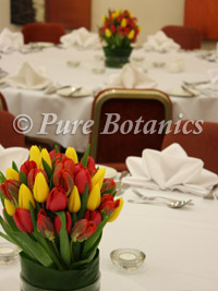 Low wedding centrepiece arrangement with tulips in yellow and red