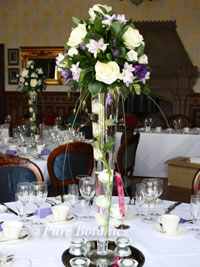 tall wedding centrepieces featuring purple wedding flowers