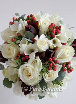 White akito roses and red hypericum berries in a wedding bouquet