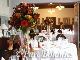 orange roses used in an autumn wedding centrepiece on the tables