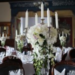 Candelabra's decorated with roses and hydrangea's for a summer wedding at Wroxall Abbey near Solihull.
