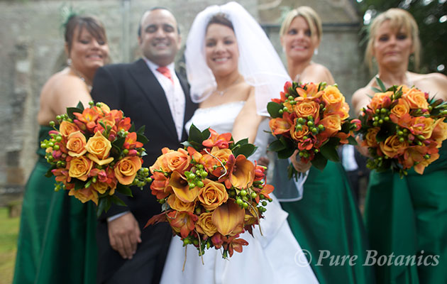 orange wedding flowers held by bride and bridesmaids