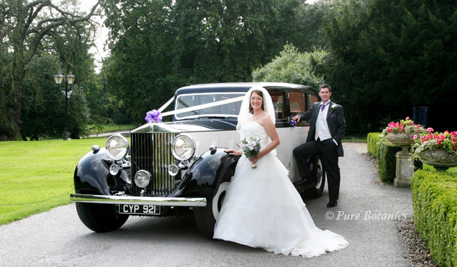 Bride holding her wedding bouquet and being photographed outside Ansty Hall with the groom.