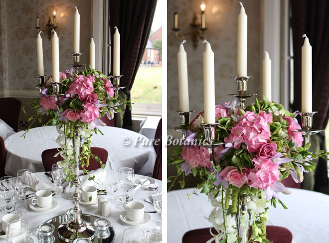 Candelabras decorated with pink wedding flowers at Walton Hall.