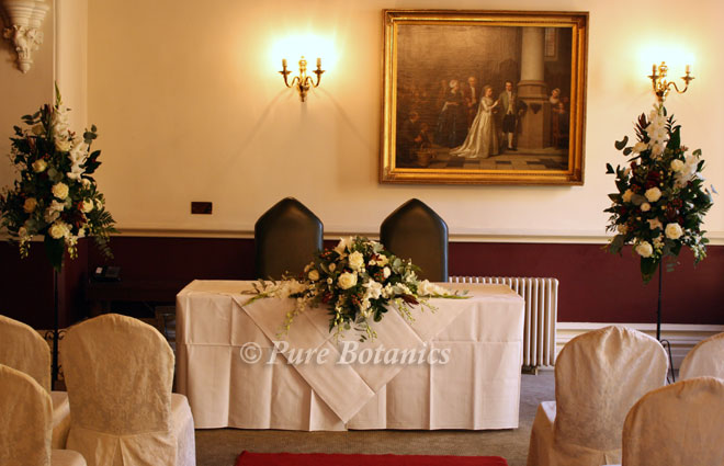The south room at Ettington Park decorated with pedestal arrangements for a wedding.