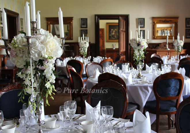 White hydrangeas arranged on candelabras at Wroxall Abbey.