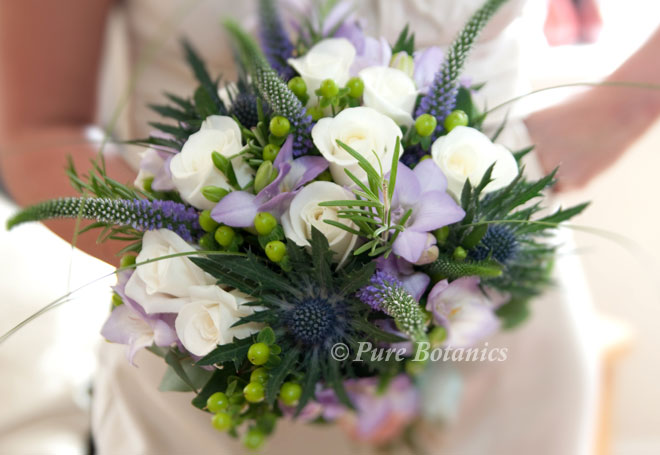 Natural bouquet with blue thistle, roses, freesias and veronica.