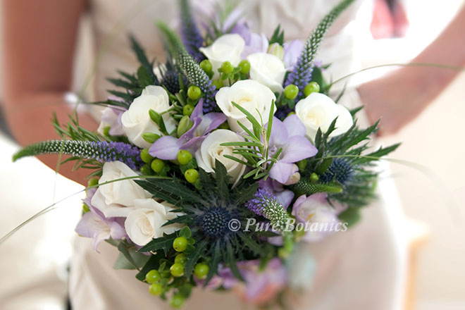 A natural bridal bouquet featuring roses, freesias, thistles and veronica in lilac and ivory.