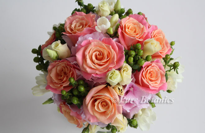 Handtied posy bouquet of cream and peach Miss Piggy roses.