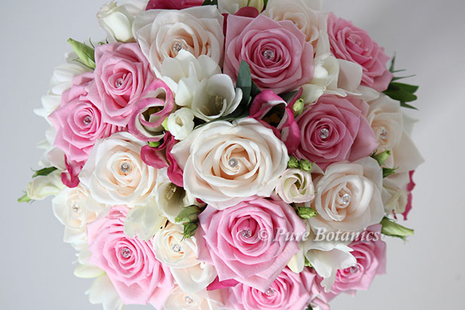 Brides posy bouquet featuring cream and pink roses with diamante pins.