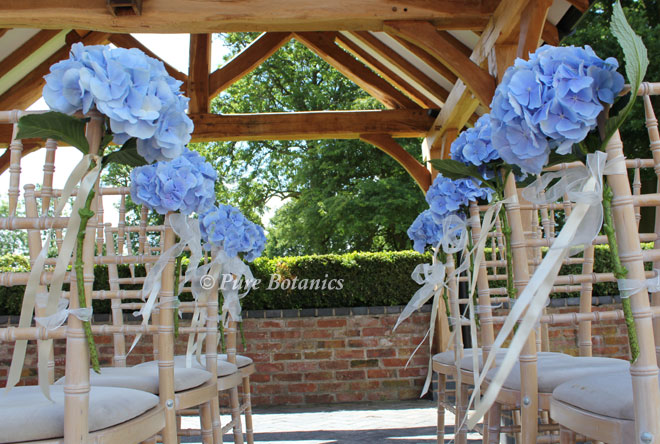 Blue hydrangeas tied to the chairs for an outdoor wedding at Wethele Manor,