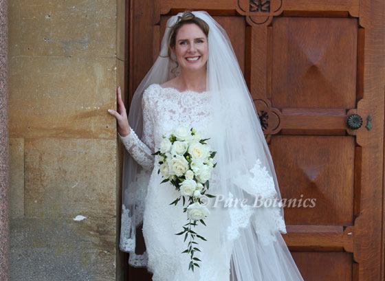 bride holding an ivory shower bouquet outside walton hall