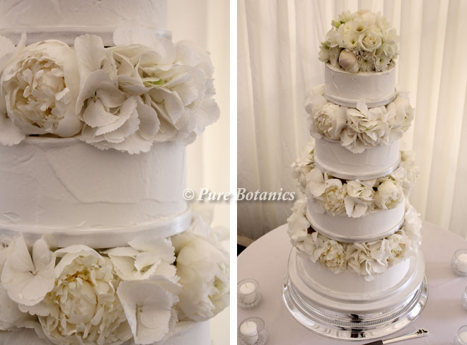 White peonies and hydrangeas placed in-between the tiers of a spring wedding cake.