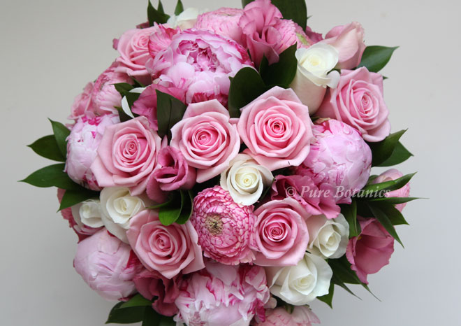 Spring bridal bouquet in pink and cream featuring ranunculus, roses and peonies.