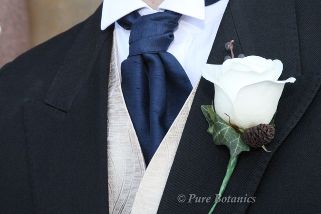 Groom's buttonhole featuring an ivory rose, pinecone and blue berries for a winter wedding.