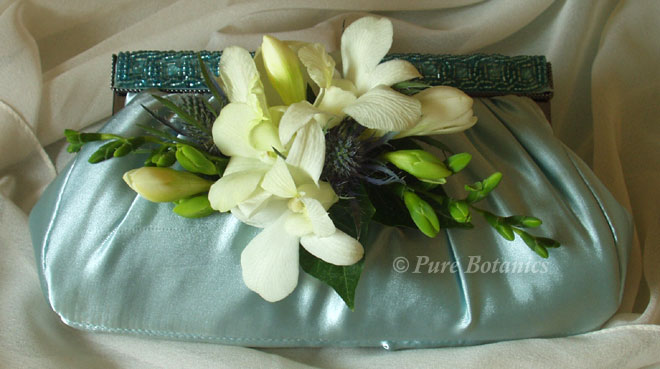 Singapore orchids and freesia's decorating a handbag.