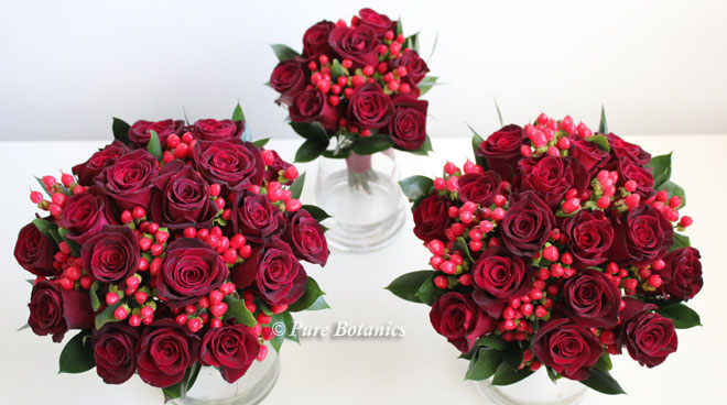 Red rose and hypericum bridesmaids bouquets for a Christmas wedding.