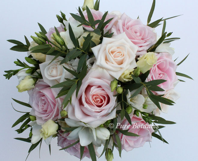 Bridal posy bouquet featuring cream and soft pink roses.