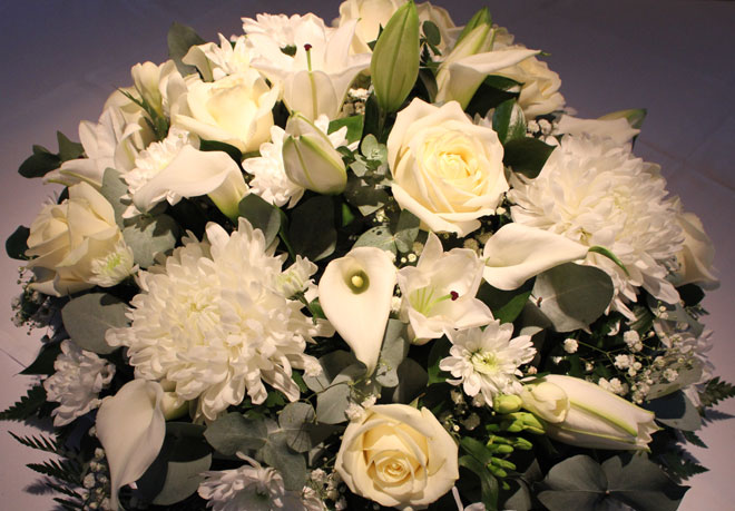 Round top table arrangement featuring white roses and calla lilies.