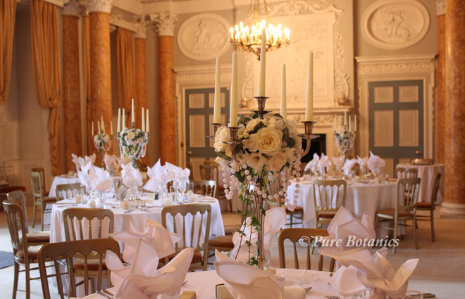 Candelabras decorated with flowers to fit in with a copper colour theme at Stoneleigh Abbey, Warwickshire.
