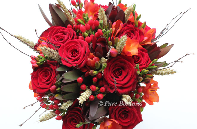 red rose and freesia bridal bouquet featuring twigs and wheat for a harvest time wedding.