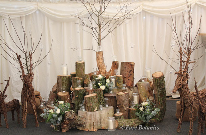 An arrangement of logs, trees, candles and flowers in a marquee.