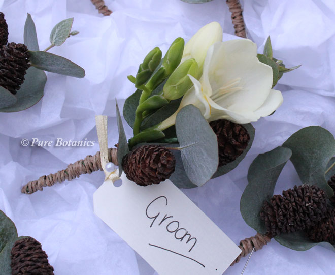 Freesias and fir cone buttonhole for the groom at a winter woodland wedding.