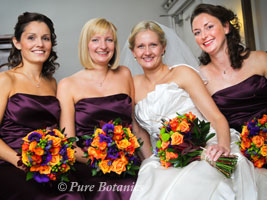 Bride and bridesmaids holding autumn wedding flower bouquets