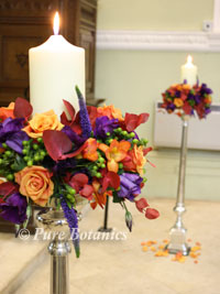 Autumn wedding flower decorations in a church featuring candles