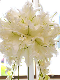close up of lilies in a tall wedding centrepiece