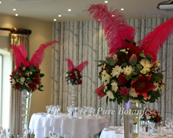 Pink wedding table decorations featuring flowers and feathers