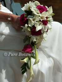 bride holding her shower bouquet featuring pink and white flowers