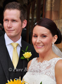yellow rose buttonhole on groom standing with bride