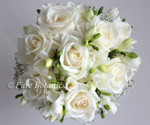 Ivory roses and freesias surrounded by gypsophila.