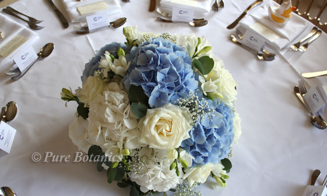 Circular top table arrangement featuring blue and ivory hydrangeas.
