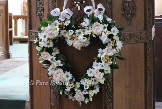 heart shaped wedding flowers on church pulpit