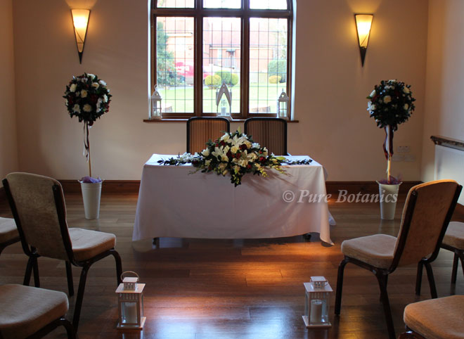 wedding flowers on registrar's table and flower trees at a wedding ceremony at Nuthurst grange warwickshire