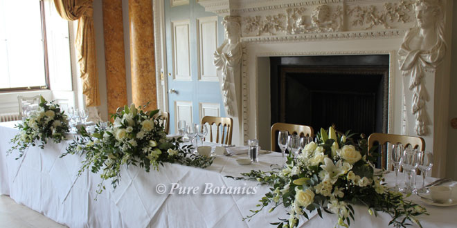 Ivory roses, lilies and gypsophila in long and low arrangements for a wedding top table.
