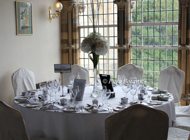 Tall wedding table decorations in the Long Gallery at Ettington Park Hotel.