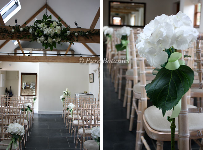 White hydrangeas decorating the chair ends on the asile at Wethele Manor.