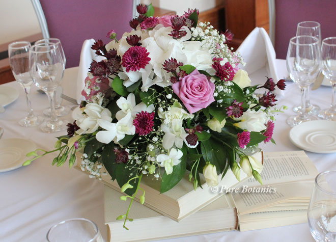 posy wedding centrepiece arranged on a pile of books.