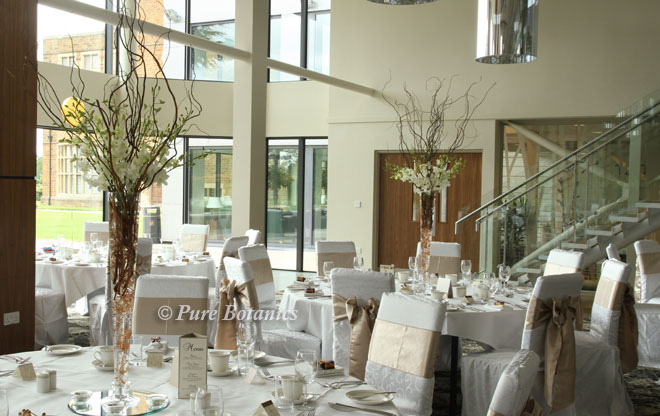 Tall wedding centrepieces featuring twigs and orchids at Ashorne Hill.